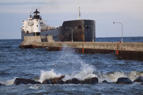 A freighter ship entering canal by lighthouse on Lake Superior.