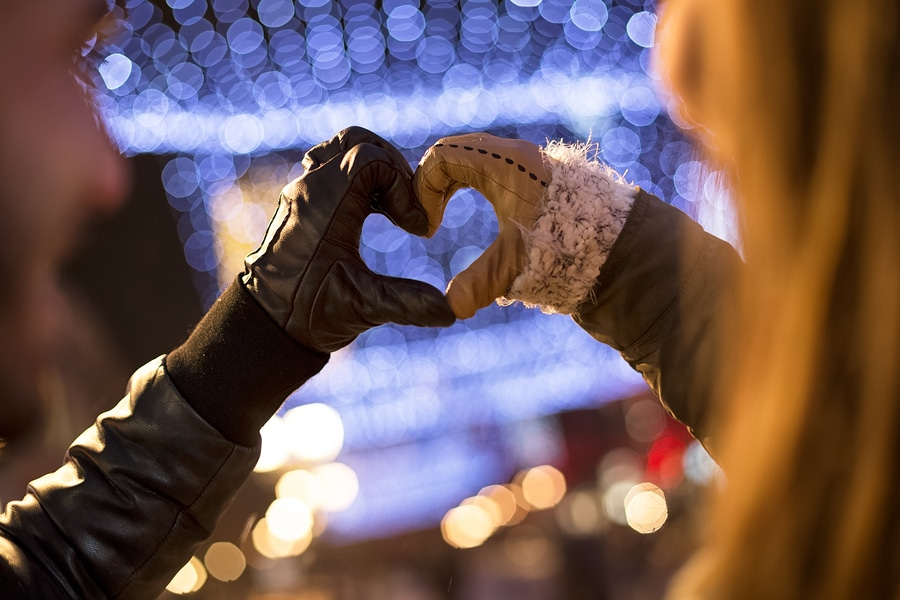 Winter background with couple making heart with gloved hands
