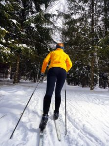 A young woman cross country skiing in a wonderful forest.