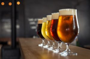 Glasses with different sorts of craft beer on wooden bar on brewery tours